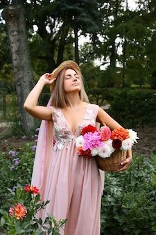 Uma garota bonita e elegante em um vestido longo e chapéu com uma cesta de flores