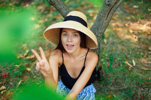 Uma garota bonita e feliz de chapéu senta-se debaixo de uma árvore, outra mostra um sinal como um retrato de close-up de vitória.