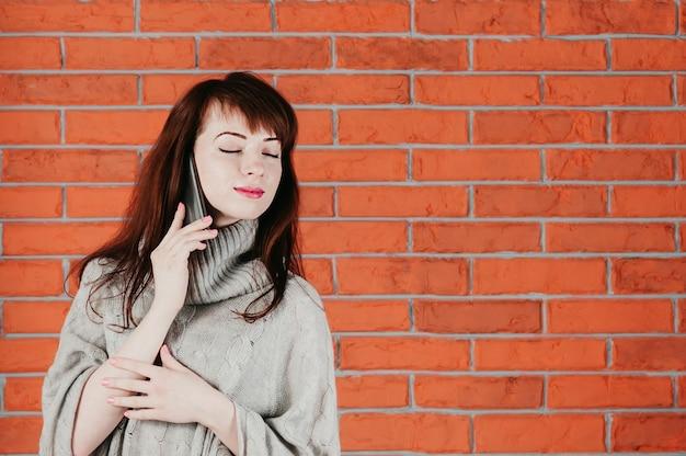 Uma garota bonita falando pelo celular, olhos fechados, sonhadoramente sorrindo