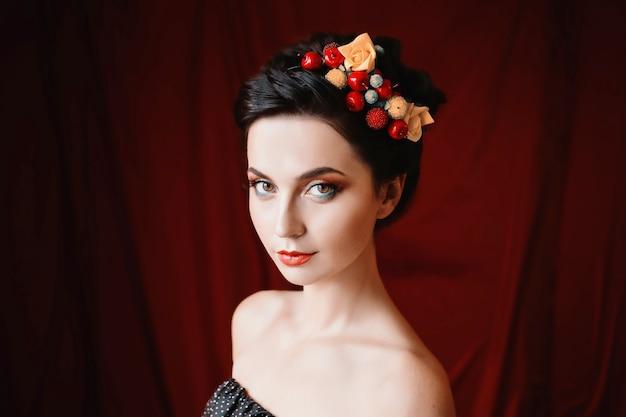 Uma garota bonita, morena com olhos castanhos com maquiagem brilhante, maquiagem com bagas e flores no cabelo, lábios vermelhos, aparência incomum, uma mulher com pele bronzeada em fundo escuro vermelho