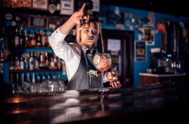 Uma garota bonita taberneiro demonstra suas habilidades no balcão de um pub