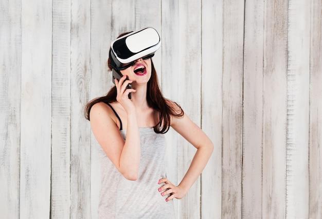 Uma garota bonita usando óculos de realidade virtual, rindo falando pelo celular