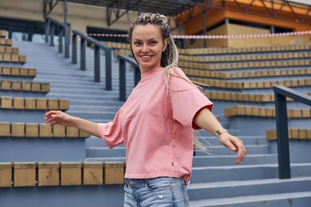 Uma garota brilhante em uma camiseta rosa girando em uma escada de pedra e sorrindo diretamente para a câmera ...