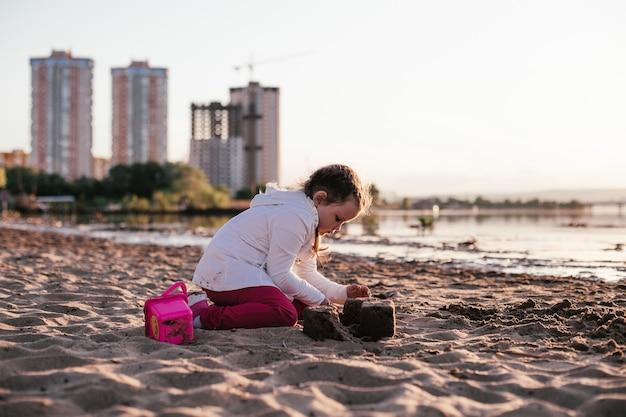 Uma garota brinca com areia em uma praia arenosa na margem do rio durante o pôr do sol.
