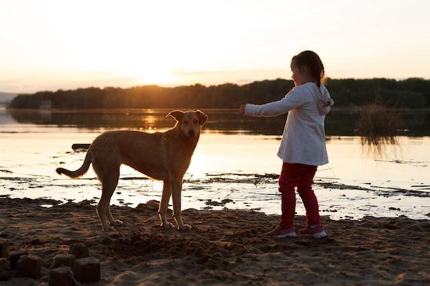 Uma garota brinca com um cachorro em uma praia à beira do rio ao pôr do sol.