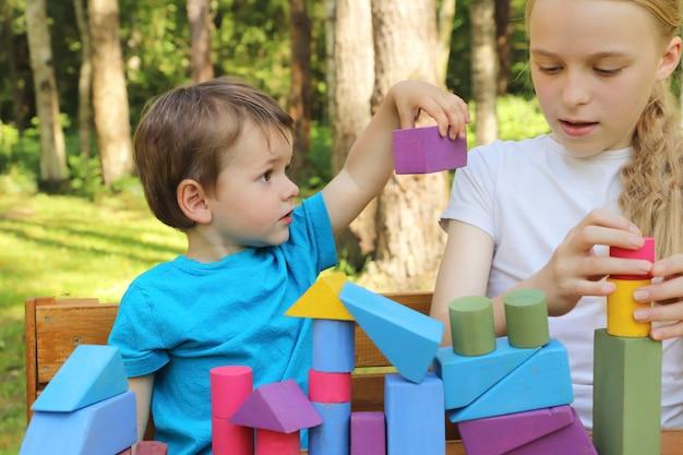 Uma garota brinca com um garotinho em cubos coloridos na natureza no verão.