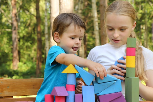 Uma garota brinca com um garotinho em cubos coloridos na natureza.