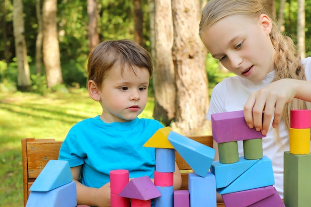 Uma garota brinca com um garotinho em cubos coloridos.