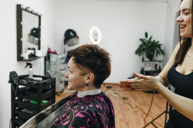 Uma garota cabeleireira faz um penteado para uma cliente em um moderno salão de beleza. a arte do cabeleireiro.