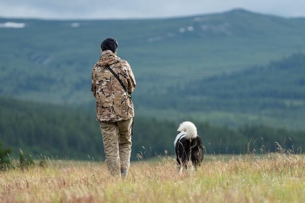 Uma garota caçadora caminha pelo campo com seu cachorro. caçando codornizes com um cachorro