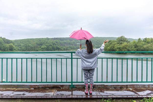 Uma garota caminha sob um guarda-chuva em tempo chuvoso em uma ponte na floresta.