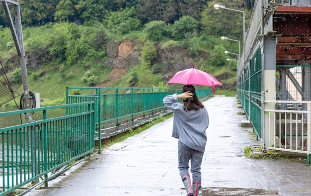 Uma garota caminha sob um guarda-chuva em um clima chuvoso em uma ponte na floresta Foto gratuita