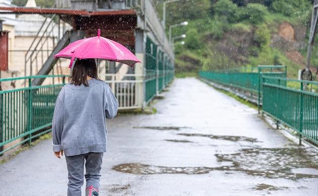 Uma garota caminha sob um guarda-chuva em um clima chuvoso em uma ponte na floresta