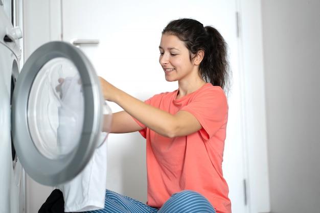 Uma garota carrega roupa suja em uma máquina de lavar enquanto está sentada no chão de um apartamento. dia de lavanderia, trabalho doméstico