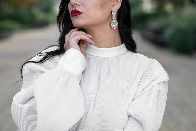 Uma garota caucasiana atraente, jovem e elegante. feche de mãos e lábios femininos. conceito de moda.