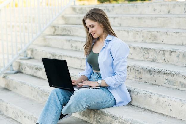 Uma garota caucasiana feliz e atraente está sentada com um laptop nas escadas. trabalho à distância. conceito freelance