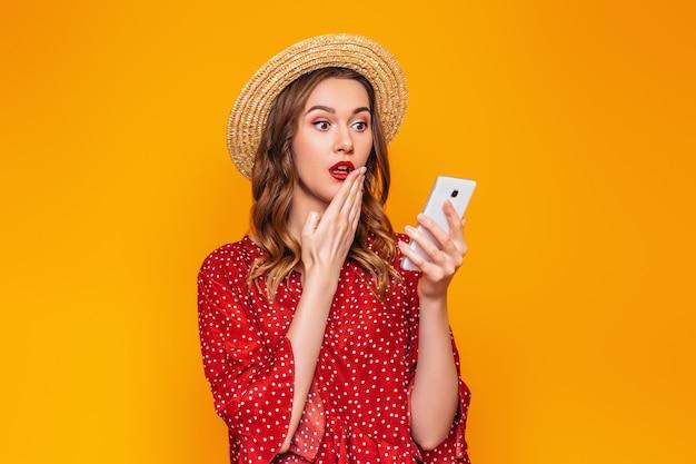 Uma garota caucasiana surpresa cobre a boca com uma mão e mantém um telefone móvel isolado em uma parede laranja. uma jovem mulher em um vestido vermelho de verão e um chapéu de palha detém uma célula de smartphone