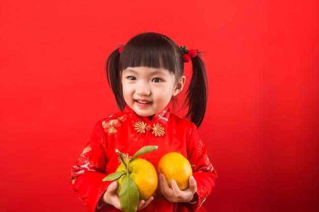 Uma garota chinesa segurando laranjas para o festival da primavera