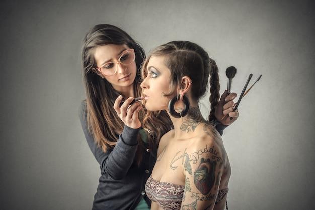 Uma garota colocando make up para outra garota