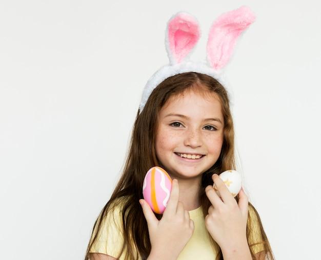 Uma garota colocou uma orelha de coelho rosa na cabeça dela.