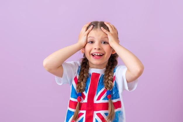 Uma garota com a imagem da bandeira inglesa em uma camiseta fica muito feliz em aprender inglês.