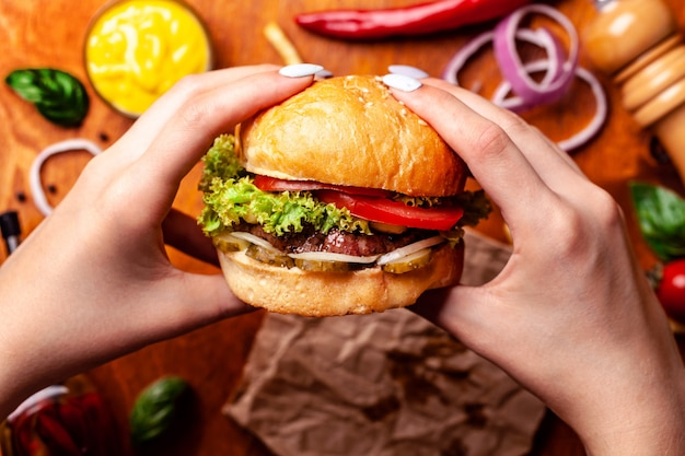 Uma garota com as mãos tem um suculento hambúrguer americano.