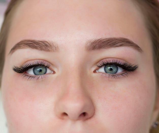 Uma garota com belos olhos verdes pintados com cílios pretos. close do rosto.