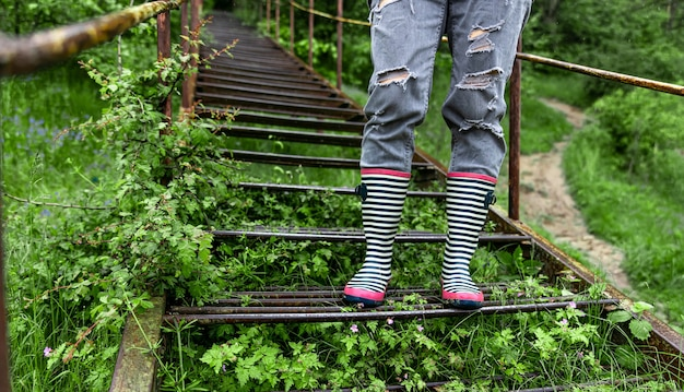 Uma garota com botas de borracha caminha na floresta em clima chuvoso de primavera close-up.
