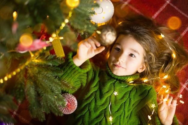 Uma garota com cabelo comprido e guirlandas encontra-se em uma manta vermelha sob uma árvore de natal com brinquedos em um agasalho de malha quente. natal, reveillon, emoções infantis, alegria, expectativa de um milagre e presentes