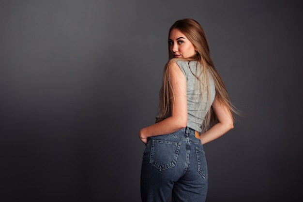 Uma garota com cabelo comprido parece por trás sorrindo, mãos nos bolsos da calça jeans em um fundo cinza sem retocar.