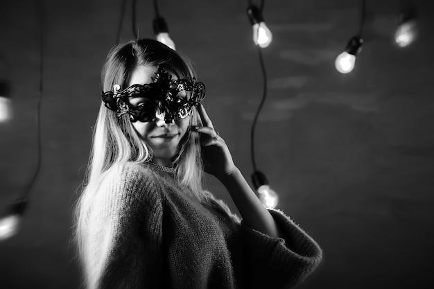 Uma garota com cabelo loiro e uma máscara preta fazendo poses