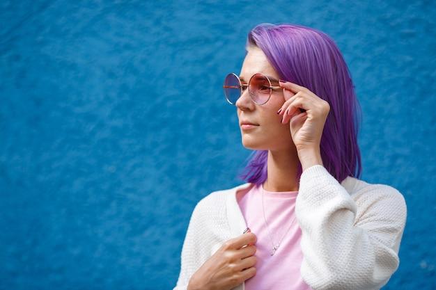 Uma garota com cabelo roxo em óculos cor de rosa
