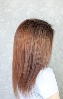 Uma garota com cabelos castanhos longos, lisos e bonitos. cuidado do cabelo em casa.