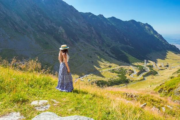 Uma garota com chapéu de palha e vestido olhando do alto para a estrada alpina transfagarasan.