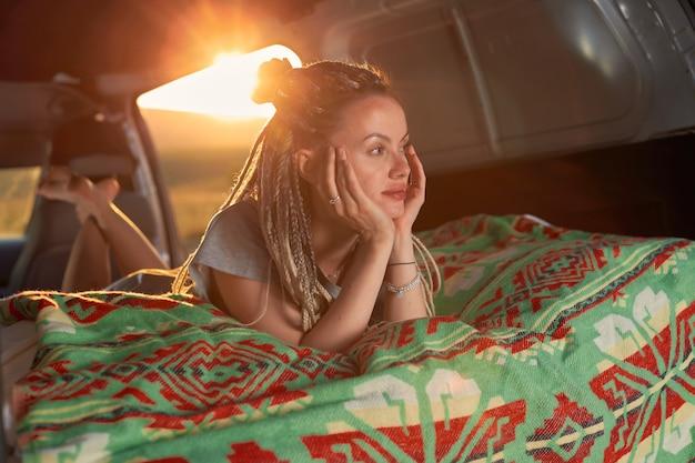 Uma garota com dreadlocks deita-se dentro do carro sobre um cobertor verde e desvia o olhar para o sol forte no b ...