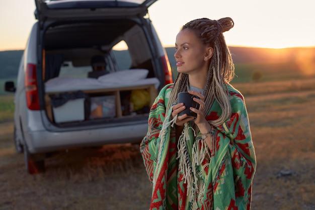 Uma garota com dreadlocks enrolada em um cobertor brilhante, segurando um copo na mão, de pé em um campo em ...