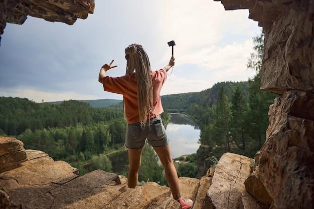 Uma garota com longos dreadlocks está em uma caverna de costas para a câmera e faz um blog sobre tra ...