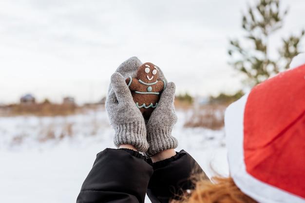 Uma garota com luvas cinzas tem um homem-biscoito nas mãos.