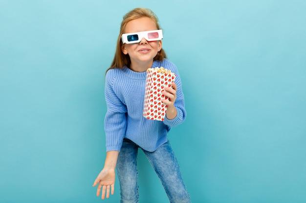 Uma garota com maquiagem e cabelos castanhos compridos, óculos 3d parece filme ou desenho animado com pipoca