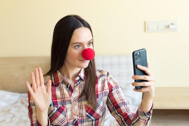 Uma garota com nariz de palhaço vermelho fica brincando na frente do telefone, tira uma selfie e dá os parabéns aos amigos