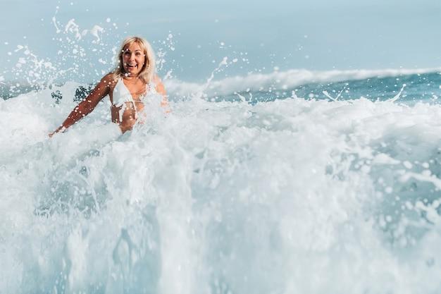 Uma garota com o cabelo molhado salta sobre grandes ondas no oceano atlântico, em torno de uma onda com respingos de spray e gotas de água.
