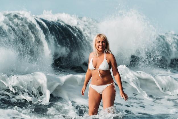 Uma garota com o cabelo molhado salta sobre grandes ondas no oceano atlântico, em volta de uma onda com respingos de spray e gotas de água. tenerife.spain.