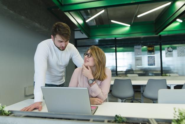 Uma garota com o marido sobre o escritório perto do laptop discute o projeto.