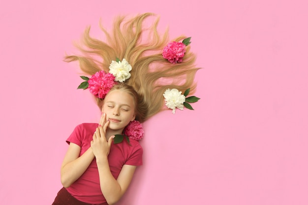 Uma garota com peônias, lindos cabelos loiros e uma colorida manicure infantil