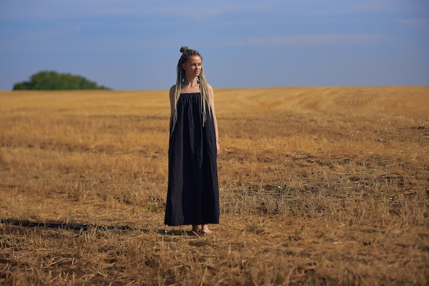 Uma garota com rabo de cavalo em um vestido preto longo está no meio de um grande campo de ...