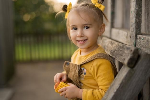 Uma garota com rabos de cavalo e laços laranja segurando uma espiga de milho nas mãos