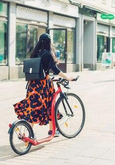 Uma garota com roupas brilhantes e uma bicicleta em uma rua da cidade, jyvaskyla, finlândia