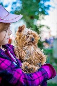 Uma garota com roupas coloridas detém uma raça de cachorro pequeno de yorkshire terrier. crianças adoram animais