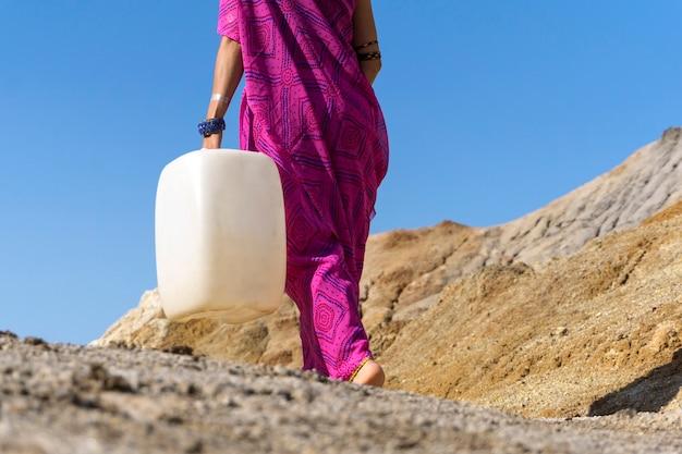 Uma garota com roupas étnicas vai buscar água com um pote de plástico