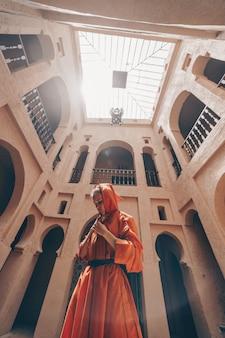 Uma garota com roupas marroquinas fica no meio do templo. o teto do templo é visível, vista inferior